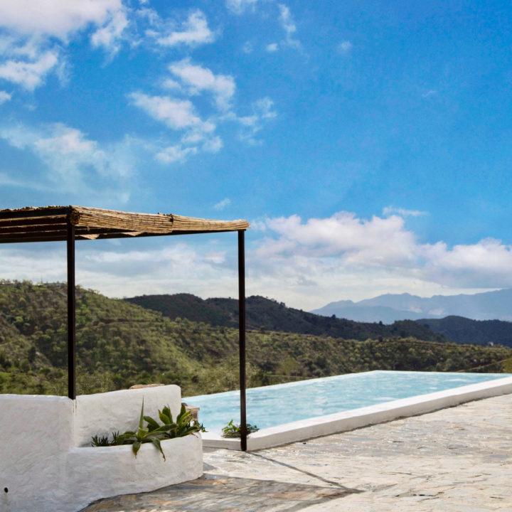 Zwembad met loungehoek en rieten schaduwdak