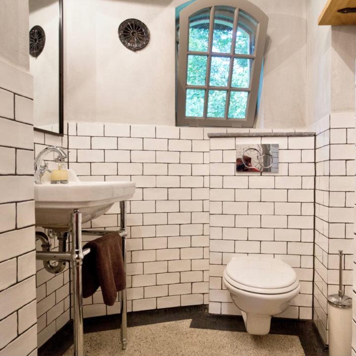 Badkamer met witte tegels, granieten vloer en toilet