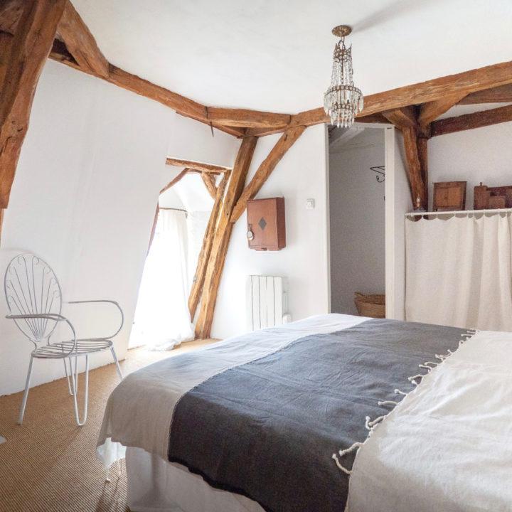 Witte slaapkamer met houten balken en bed