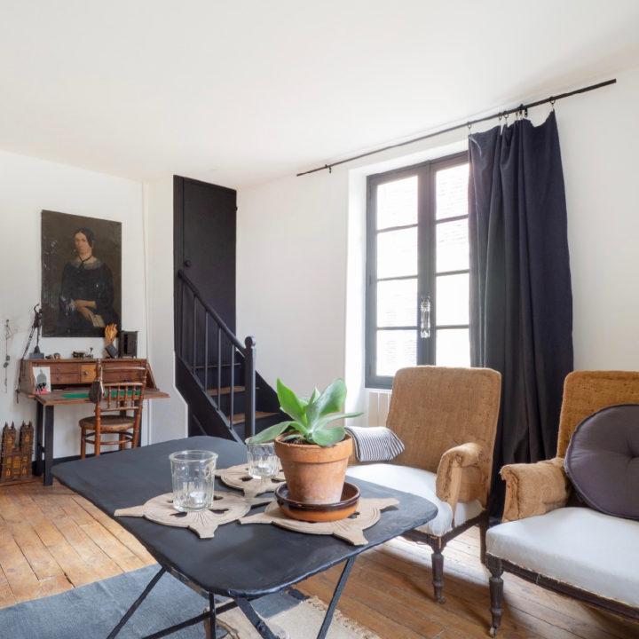 Woonkamer met zwart metalen salontafel en fauteuils