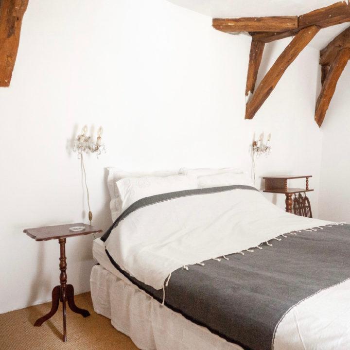 Tweepersoons bed met wit linnen in slaapkamer met houten balken