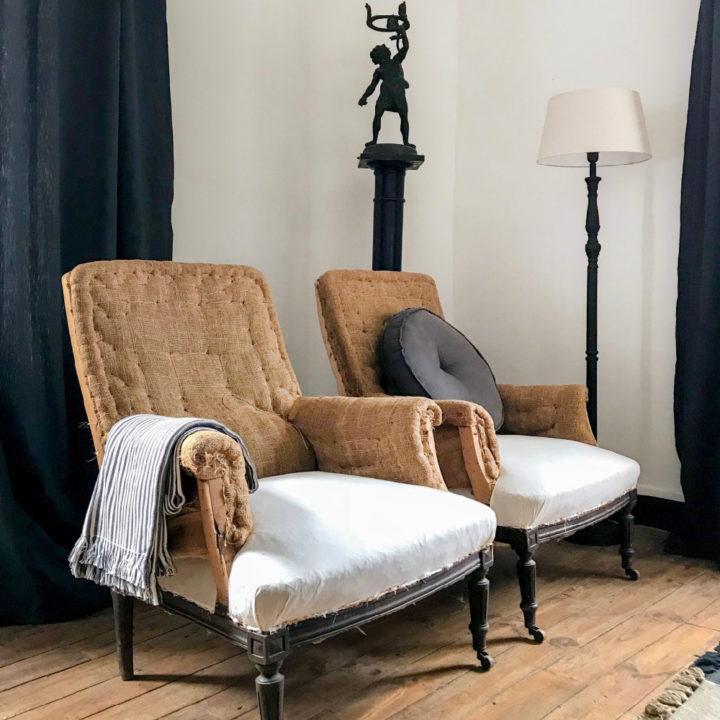 Ouderwetse fauteuils met wit en bruin, grijze plaid erover