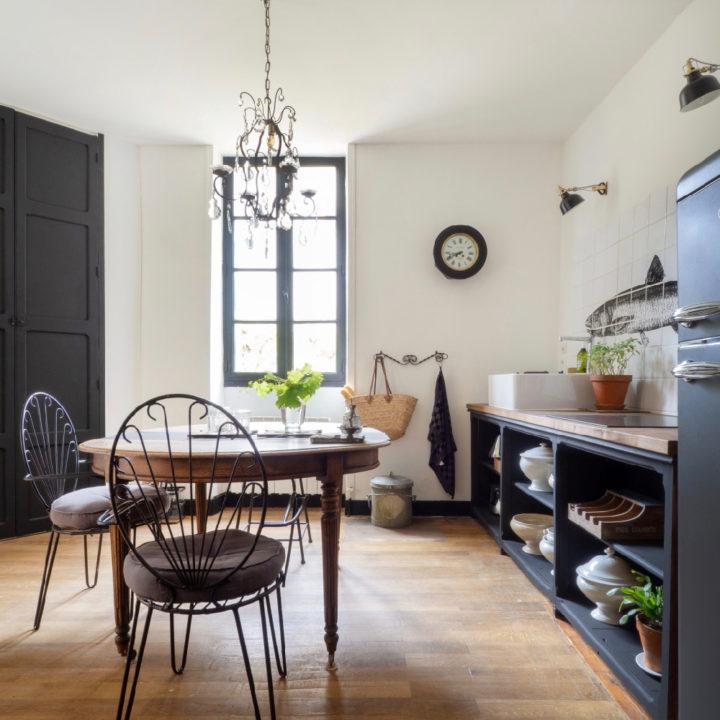 Woonkeuken in zwart met ovale tafel met metalen stoeltjes