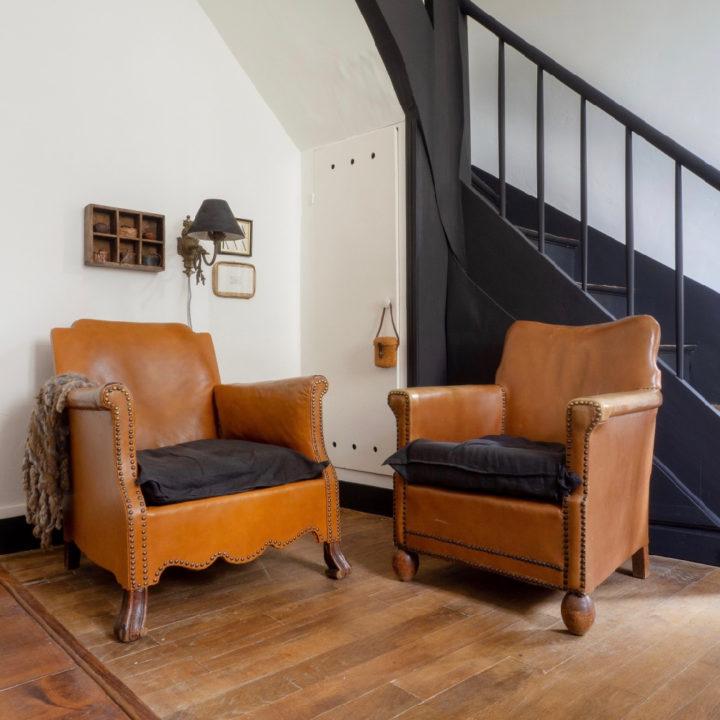 Twee leren fauteuils met bruine kussens naast een zwarte trap