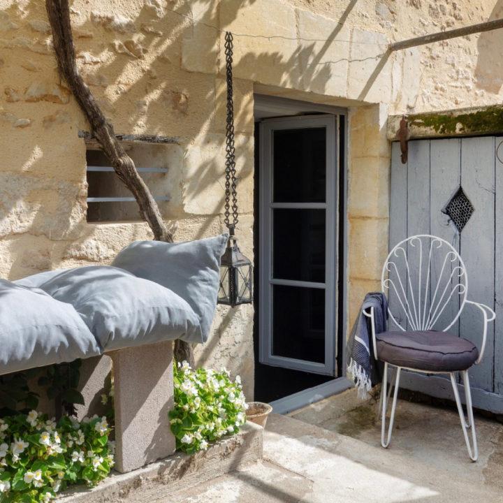 Terrasje bij huis, met gietijzeren stoeltje en bankje met grijze kussens