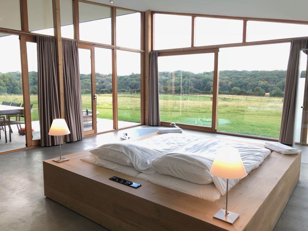 Een groot tweepersoons bed gericht op de grote ramen met uitzicht over de weilanden