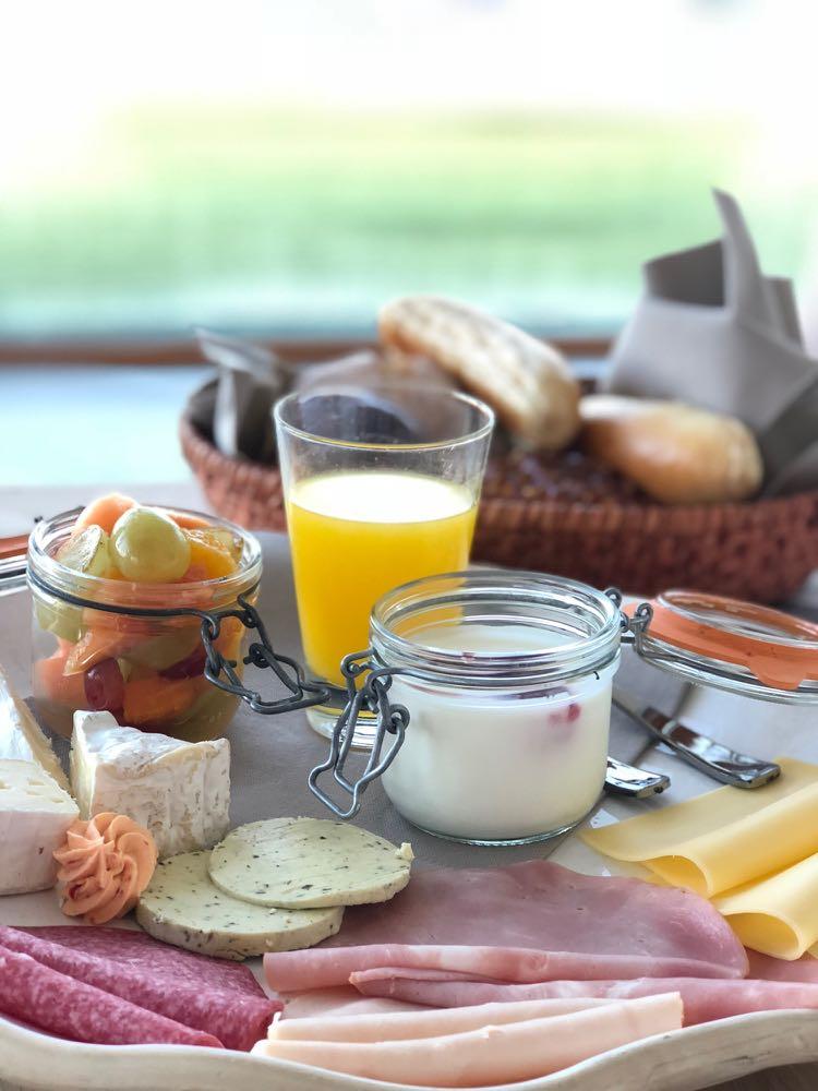 Ontbijt met sinasappelsap, yoghurt, broodjes en beleg.