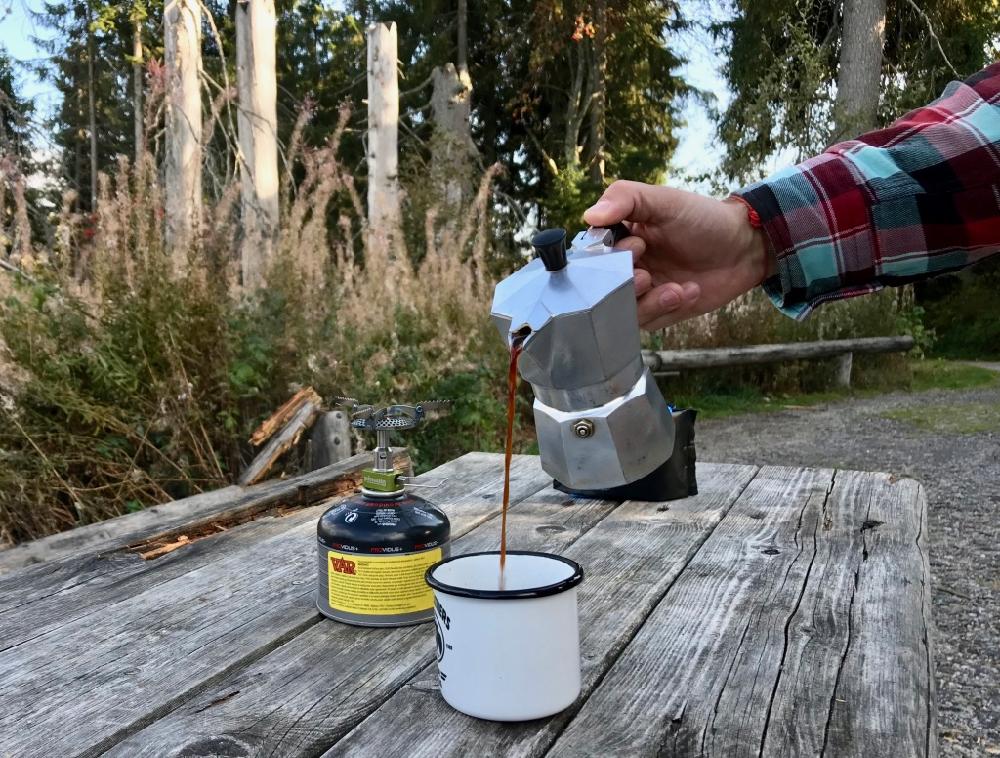 Een koffie zetten tijdens je wandeling, met emaille mokken op een picknicktafel