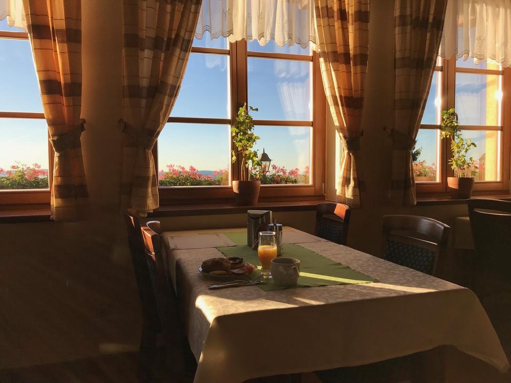 Tafel voor het raam met gordijnen, waardoor het zonlicht naar binnen valt.