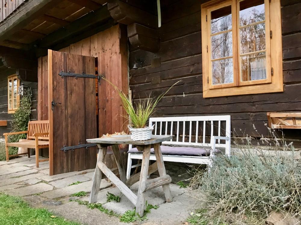 Een zitje voor het vakantiehuis, met een bankje en tafel