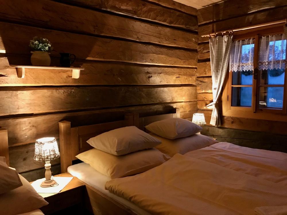 Romantische en knusse slaapkamer in vakantiehuis, met houten wanden en mooi opgemaakt bed