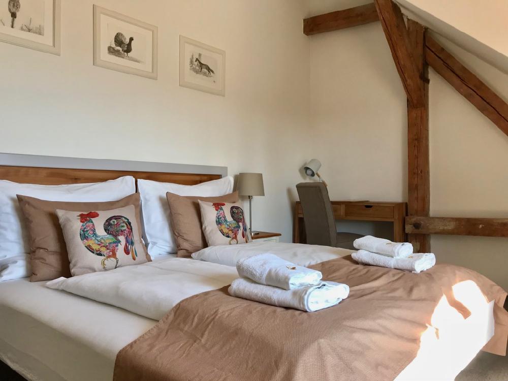 Hotelkamer met opgemaakt bed met handdoeken en kleurrijke kussens erop