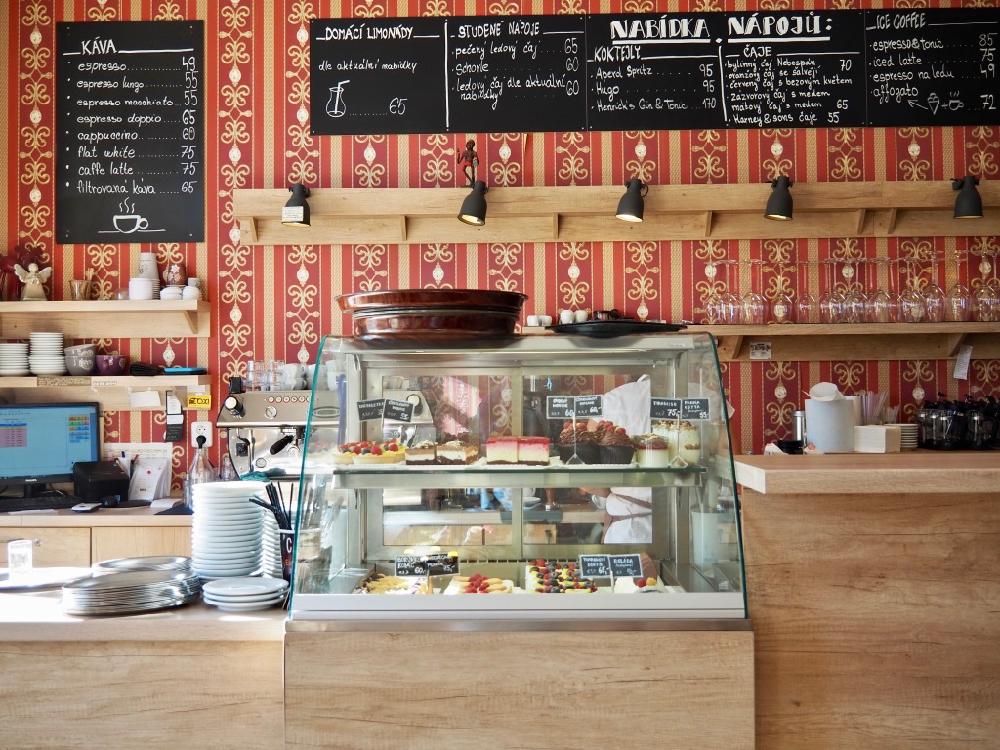 Vitrine met taartjes en een kleurrijk behang met daarop krijtborden met het menu