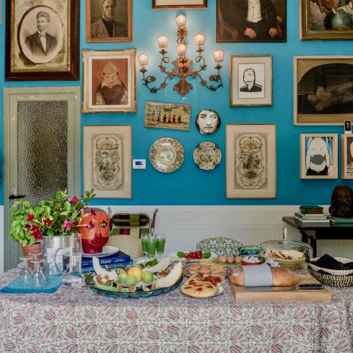 In de kleurrijke eetkamer met een blauwe wand vol schilderijen