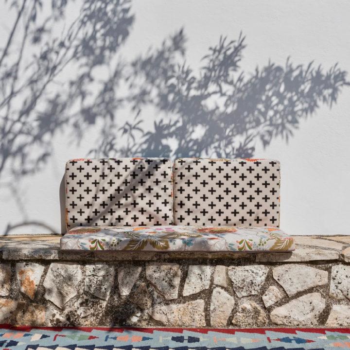 Een stenen bank met kussen voor een trullo bij Anima B&B