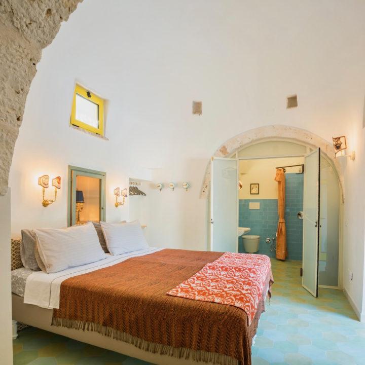 Interieur van een trullo met tweepersoons bed en badkamer op de achtergrond