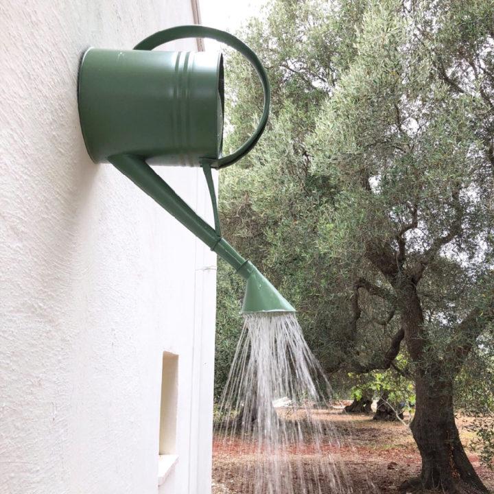 Een groene gieter op een witte muur, als buitendouche