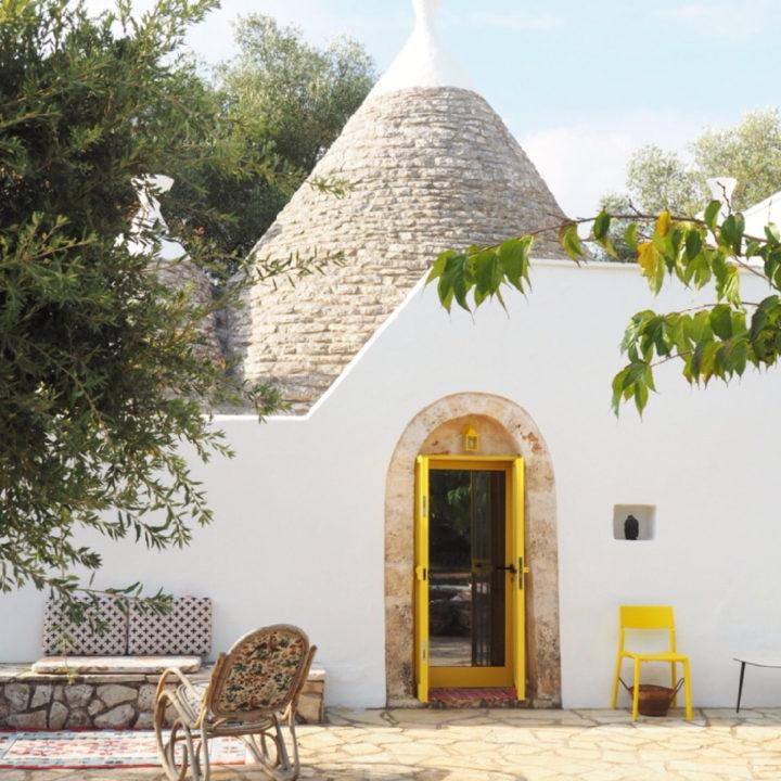 Een witte trullo met gele deuren, een bankje naast de ingang en een rotan stoel