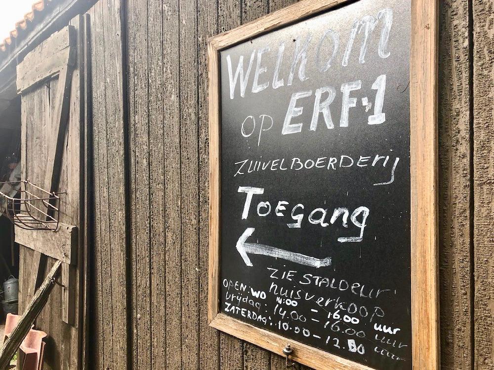 Welkom bij Erf 1: een krijtbord met tekst op de schuur van de boerderij