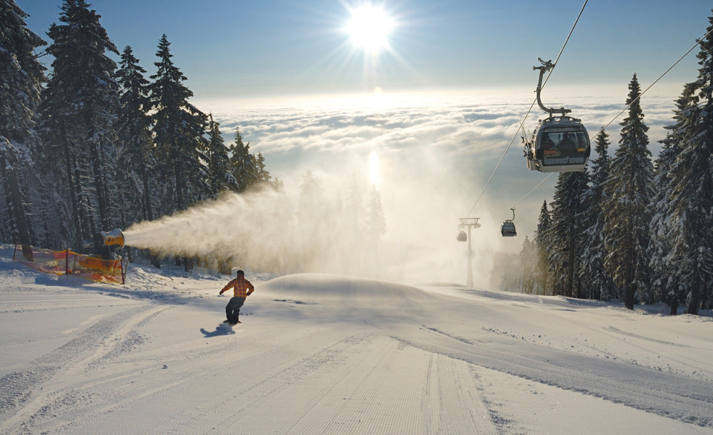 Een piste met tegenlicht, een skiër, cabinelift en een sneeuwkanon