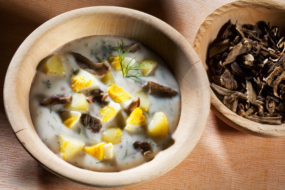 Een bord soep in een houten kom, met paddestoelen