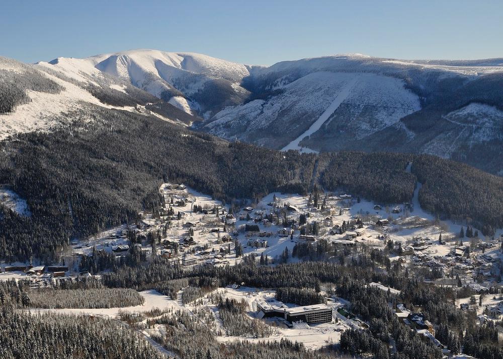 Een zicht op een dorp in een dal, tussen de dennenbomen en pistes, in de winter