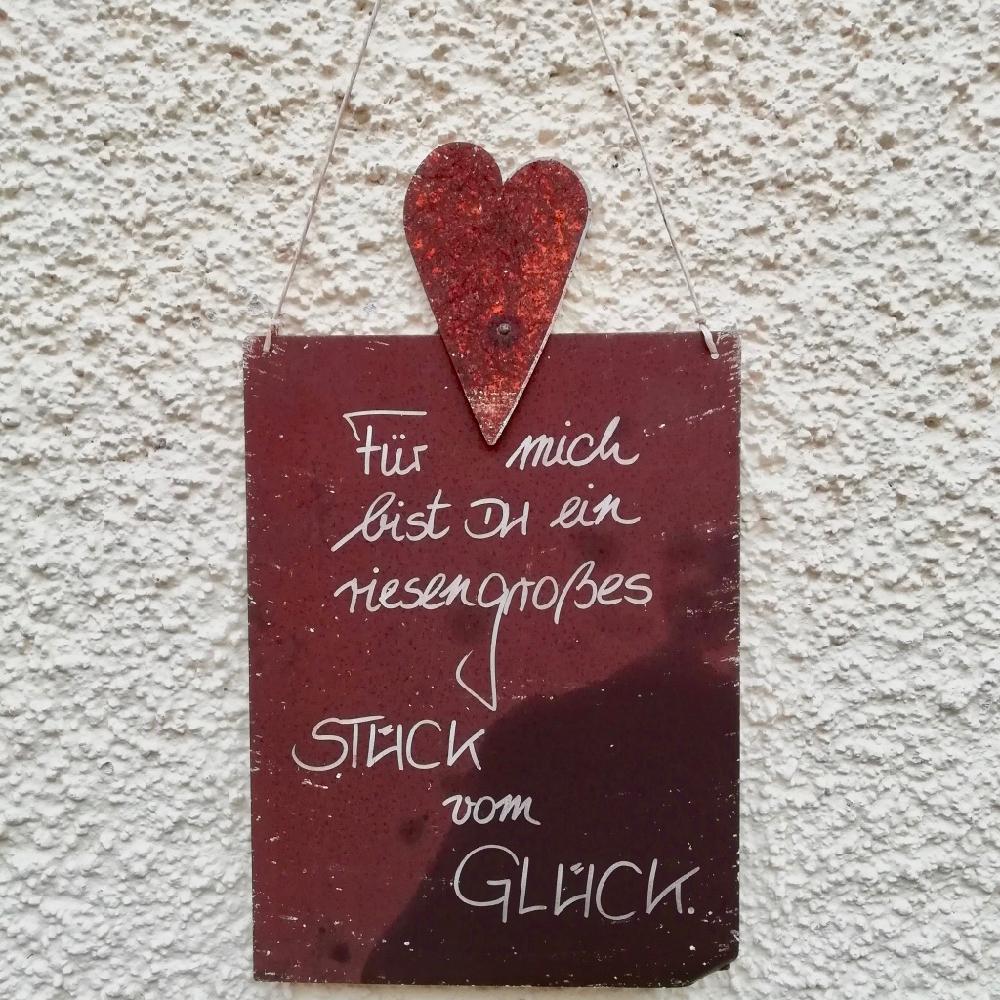 Een rood houten bordje op een witte muur