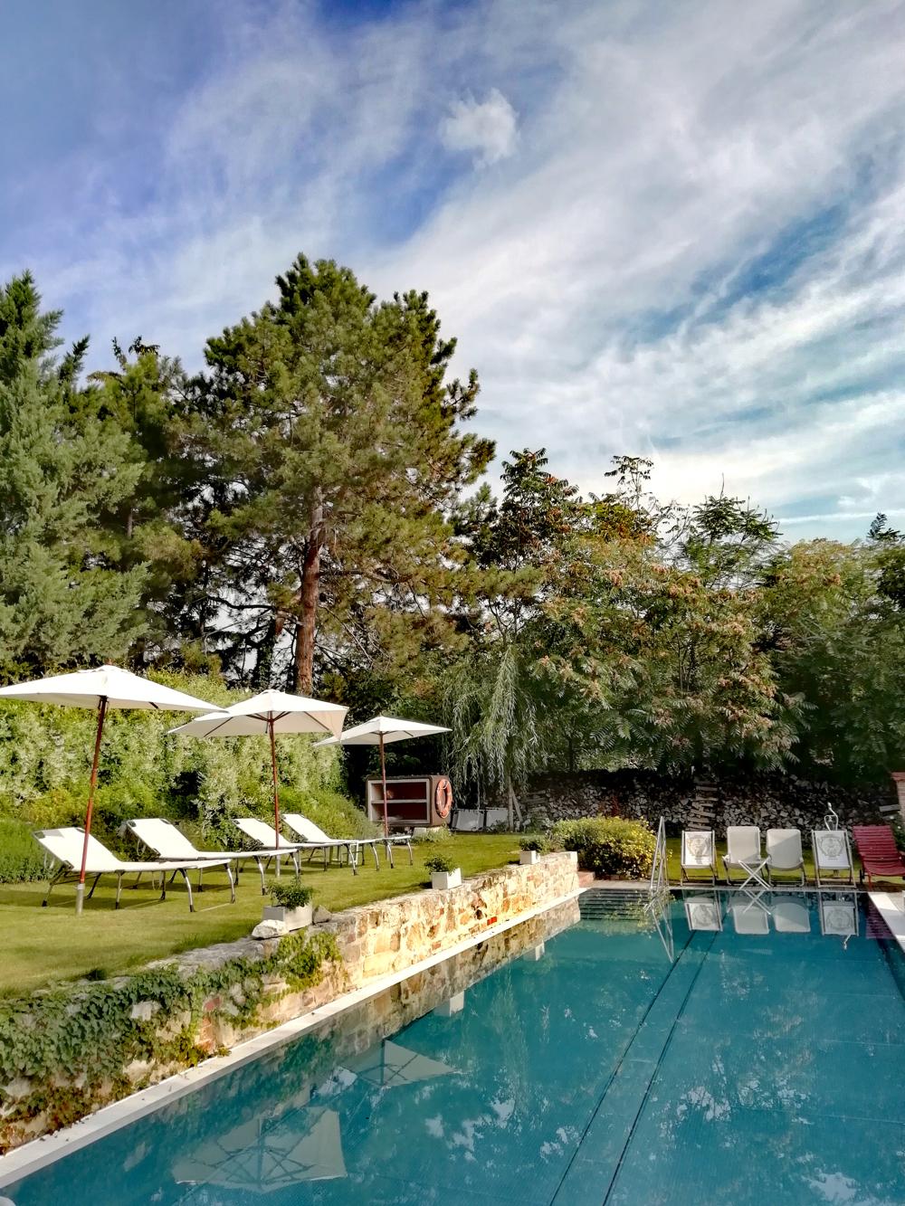 Zwembad met witte ligstoelen op groen gras