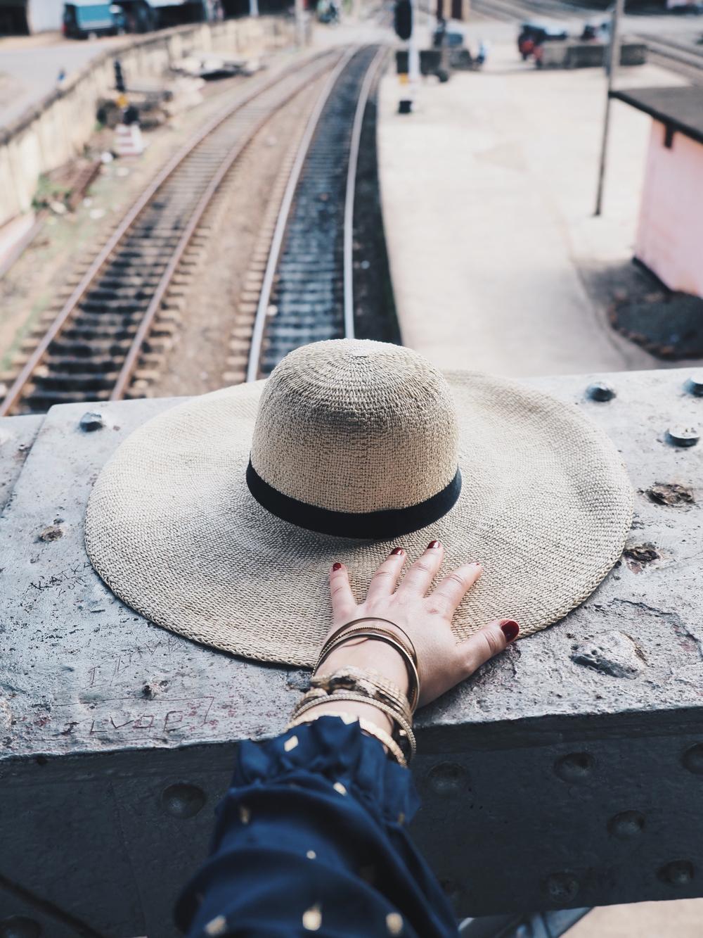 Een rieten hoedje op een betonnen muur van de spoorbrug, de hand van Anne en het spoor