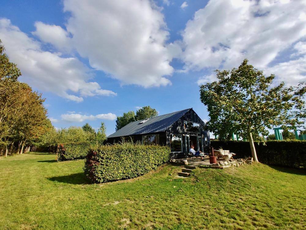 Vakantiehuis in het groen, zwart van buiten, een mooie wolkenlucht