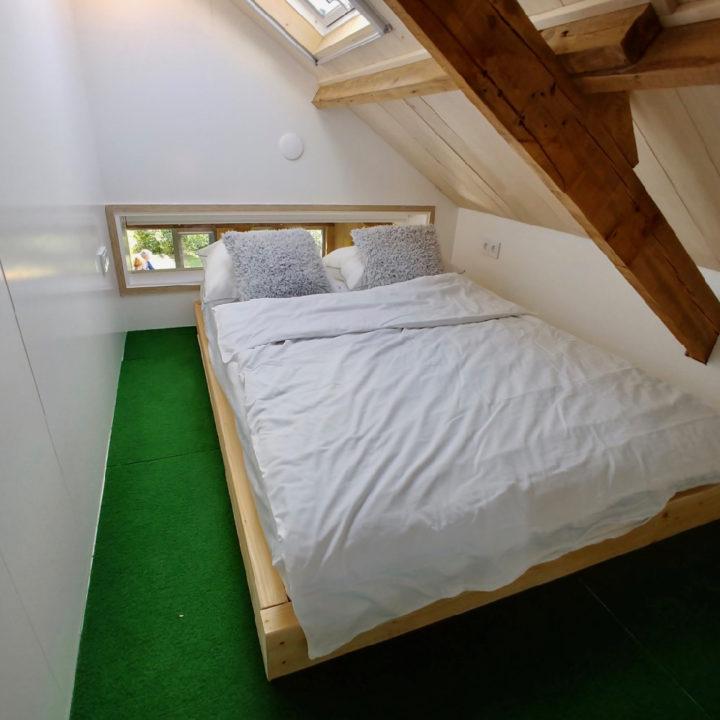 Bedstede met opgemaakt bed met wit beddengoed en graskleurig tapijt
