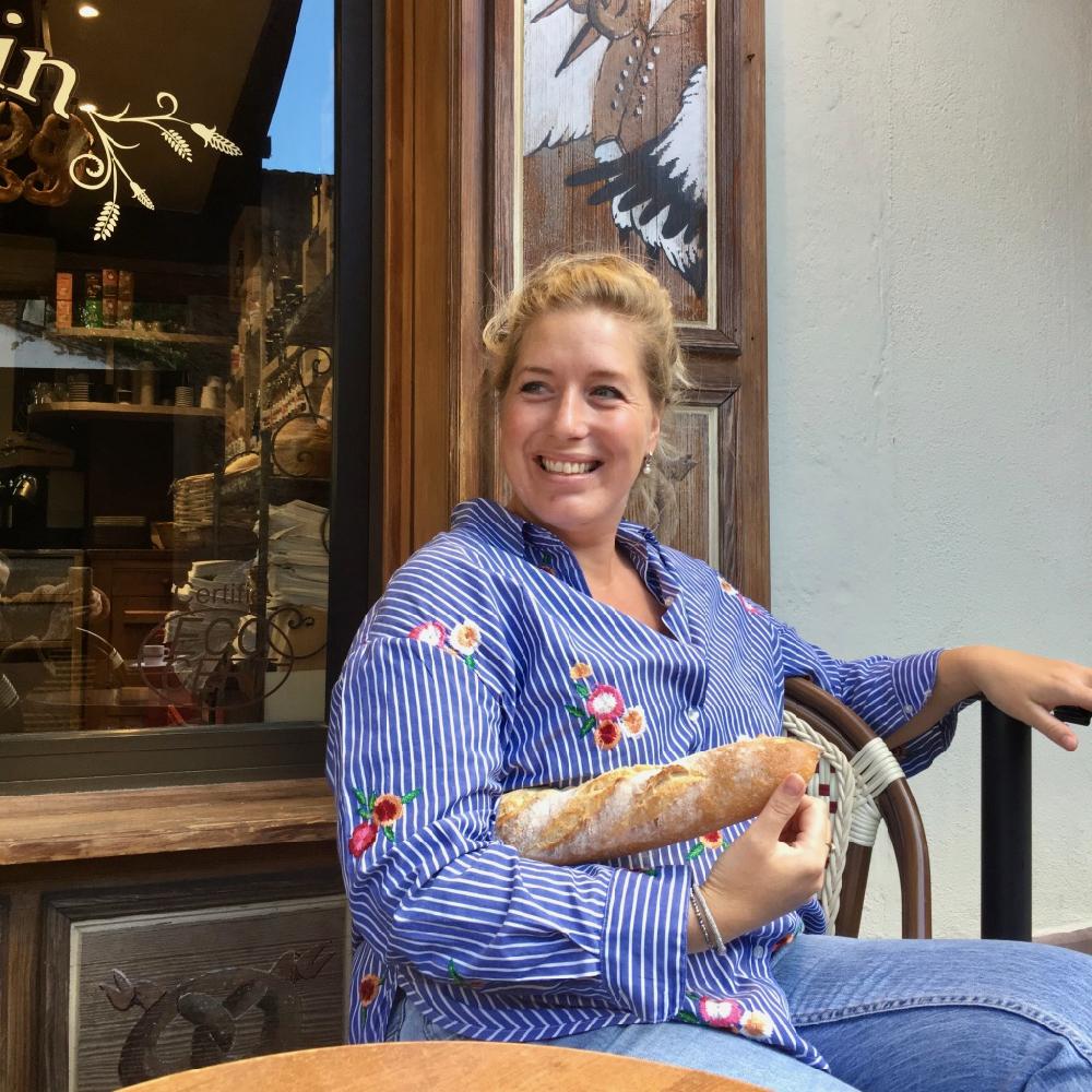 Jorieke op een terras in de Elzas, met een stokbrood onder haar arm