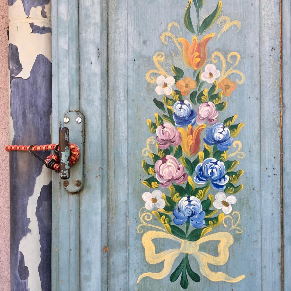 Geschilderde bloemen op een metalen deur
