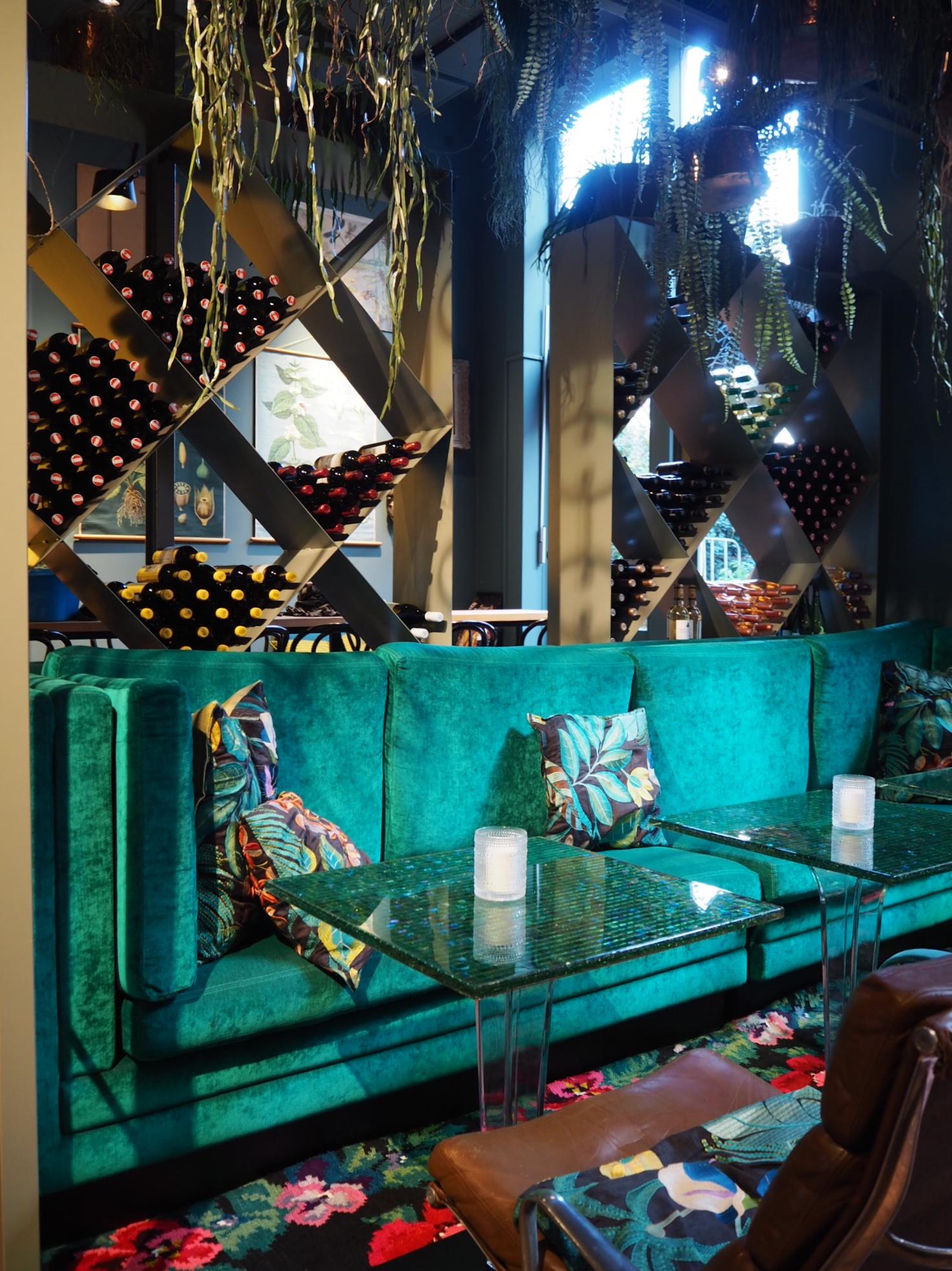 Een groene fluwelen bank met glazen tafels en wijnflessen in grote vierkante rekken