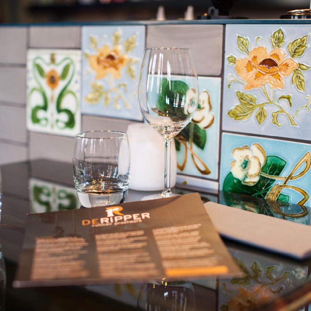 Menukaart van De Rippers op een tafels met tegeltjes met bloemen erop