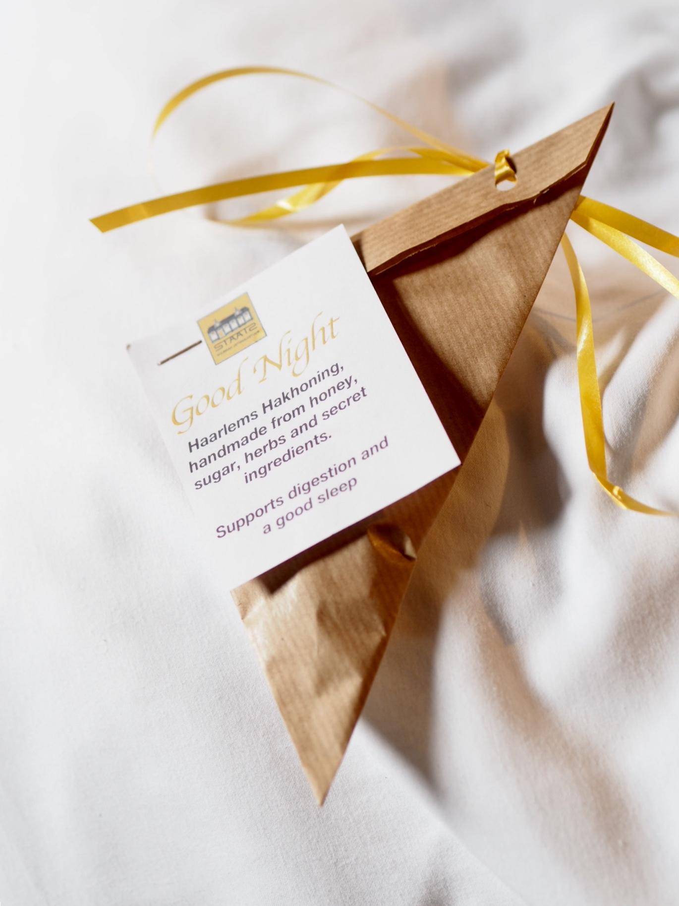 Een papieren zakje met geel lint en een tekstje dat honing rustgevend werkt, voor het slapen gaan.