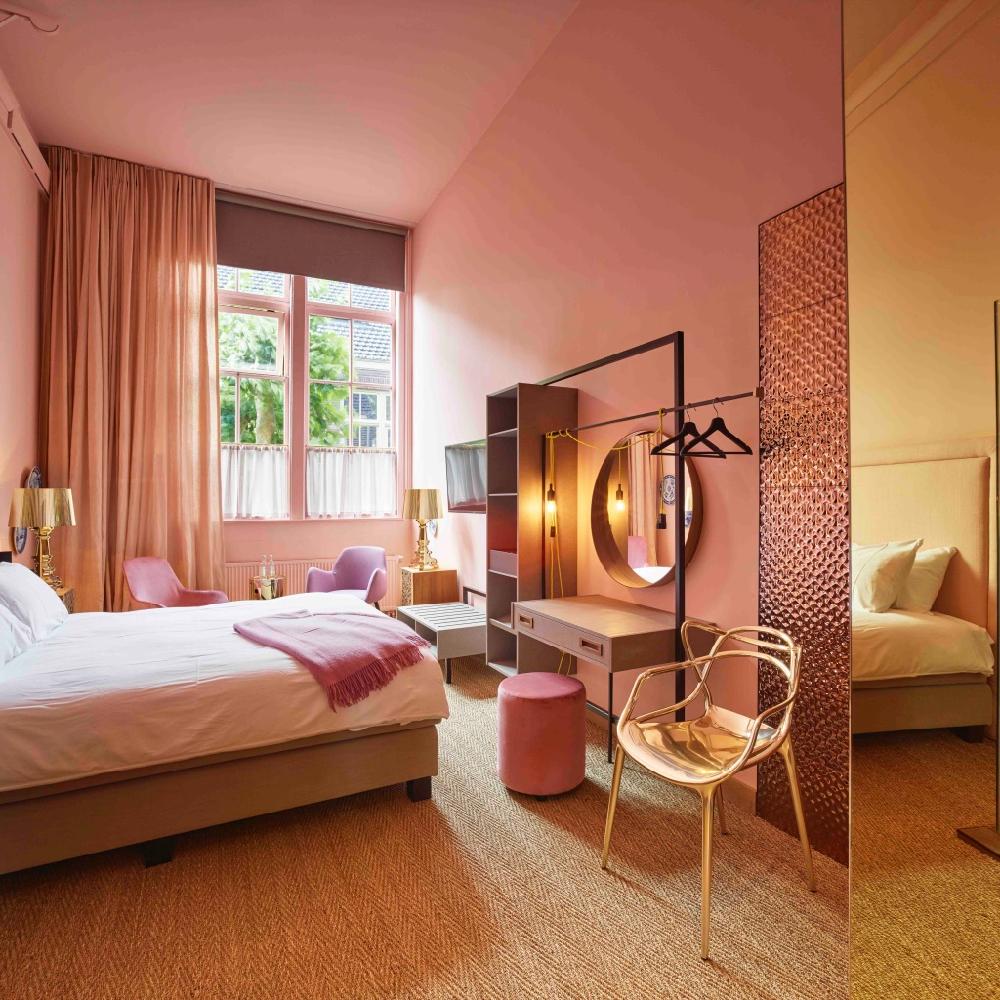 Een roze deluxe tweepersoons kamer in boutique hotel Staats