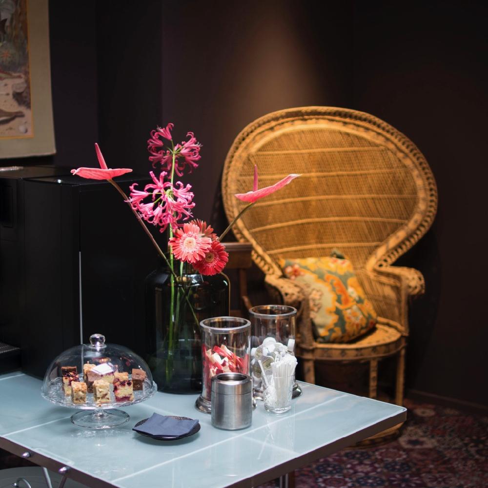 Een tafel met koffie apparaat en snoepjes, een bloemetje erop en rieten rotan stoel ernaast