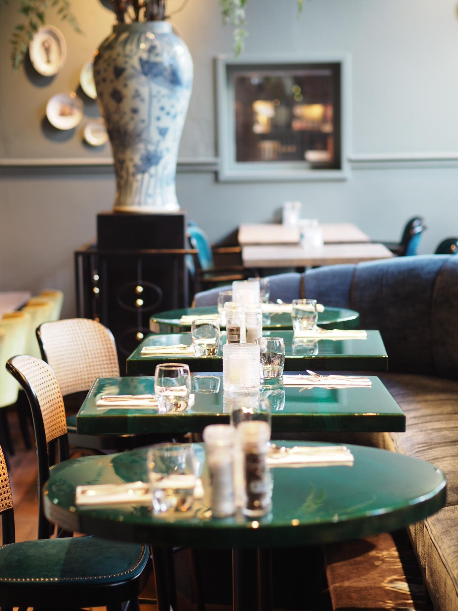 Groene tafeltjes met houten stoelen in restaurant Rippers van hotel Staats