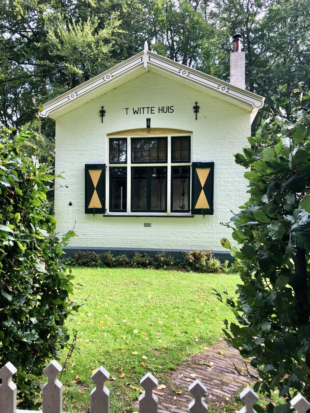 Een zit huisje met groen/gele luiken in het groen