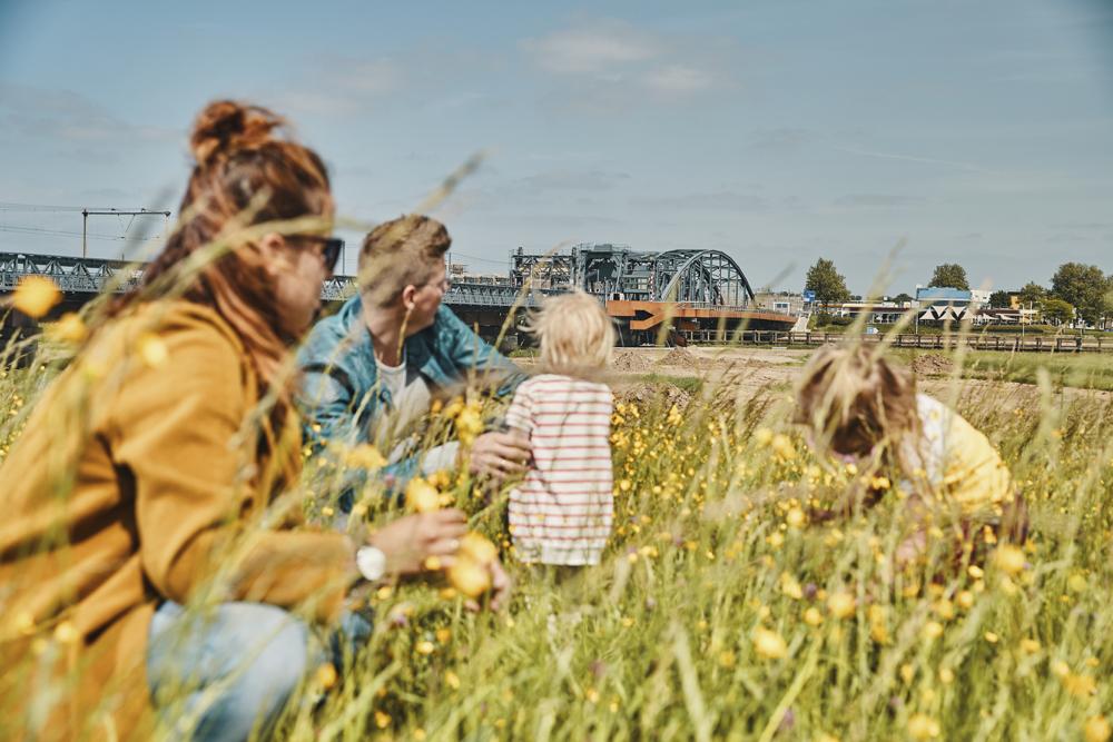 Een gezin met twee kindjes tussen de bloemen in het gras, met op de achtergrond de oude IJsselbrug