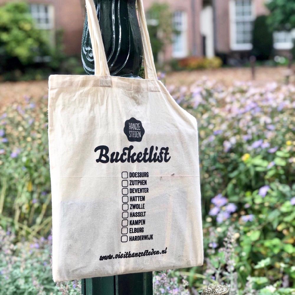 Een linnen tas met daarop de namen van 9 Hanzesteden