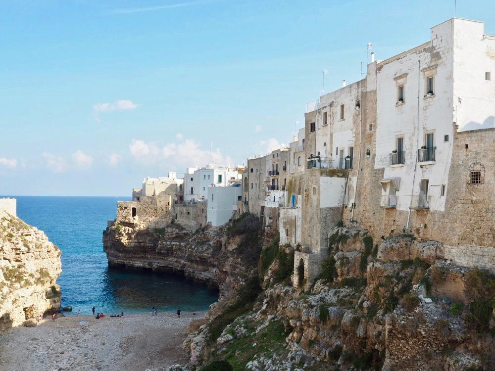 Witte huizen op een rots en een azuurblauwe zee