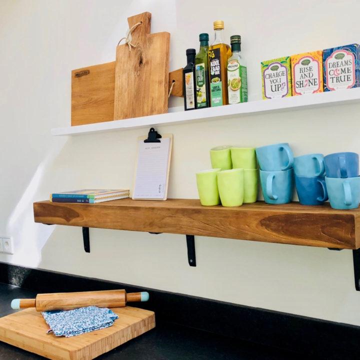 Schappen aan de muur met houten planken, mokken en thee