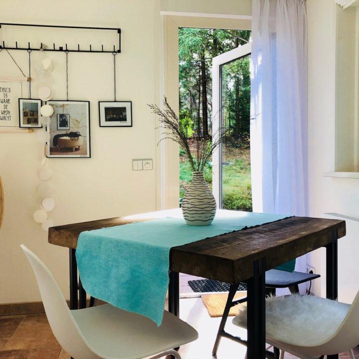 Een donkere houten tafel met een mintgroen kleedje en witte eetstoelen.