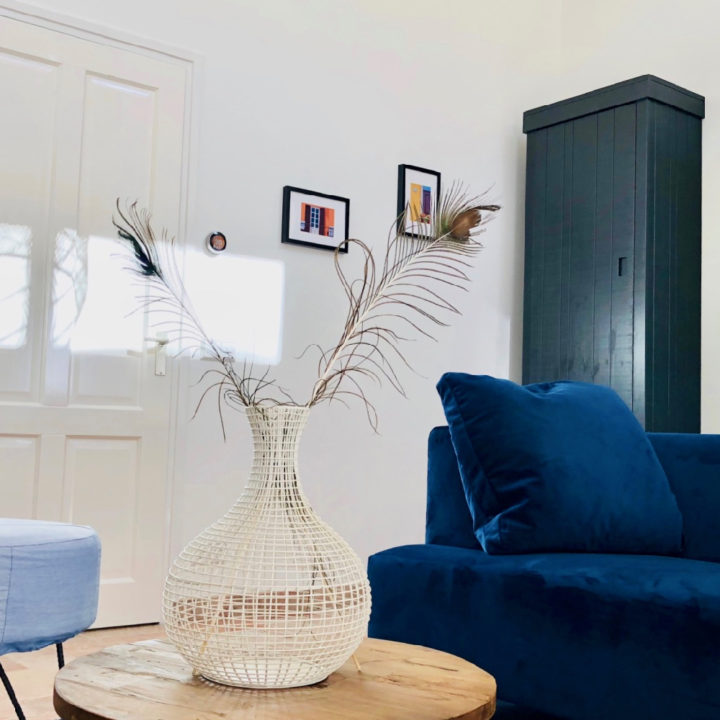 Lichte woonkamer met blauwe bank, ronde houten tafel en lichtblauwe poef.