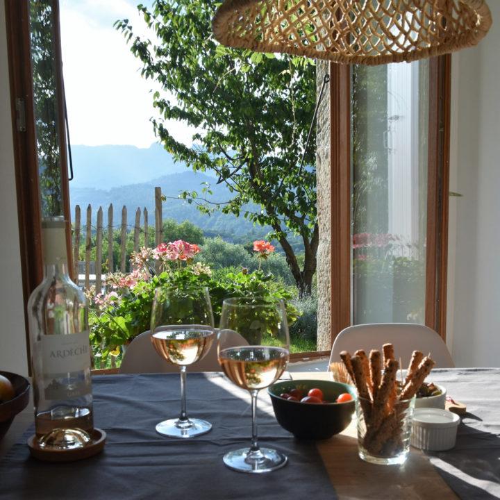 Tafel met glazen rosé, kaasstengels en hapjes, voor een openstaand raam waardoor het zonlicht binnenvalt.