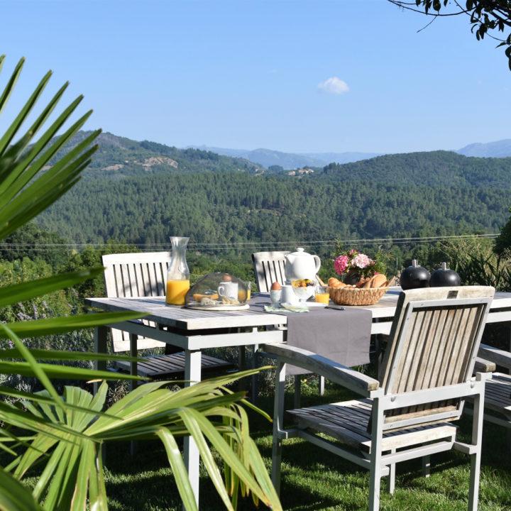 Ontbijt aan een houten tuinset, met uitzicht over de heuvels