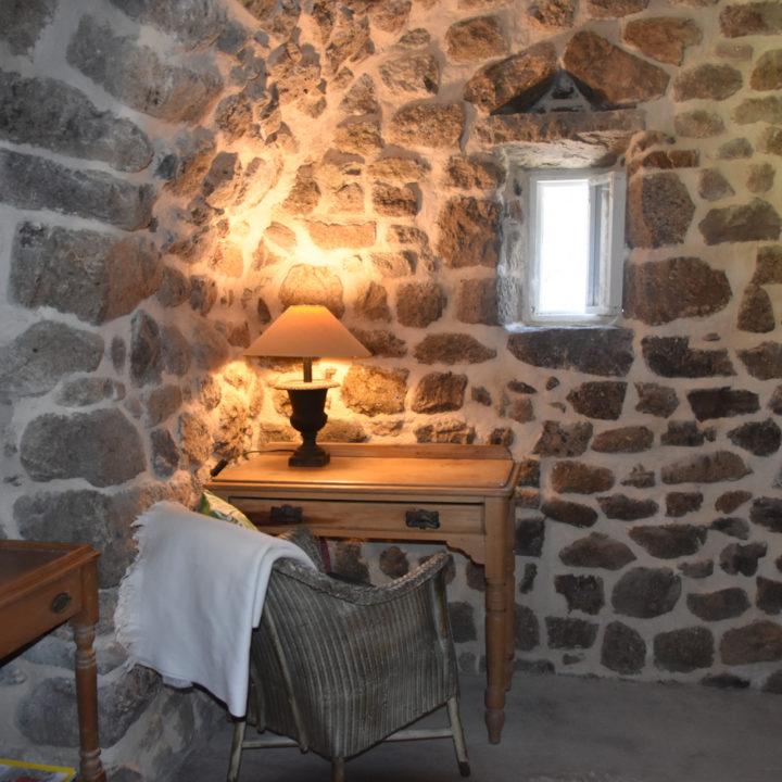 Houten tafeltje met rieten stoel tegen een authentieke en stoere stenen muur