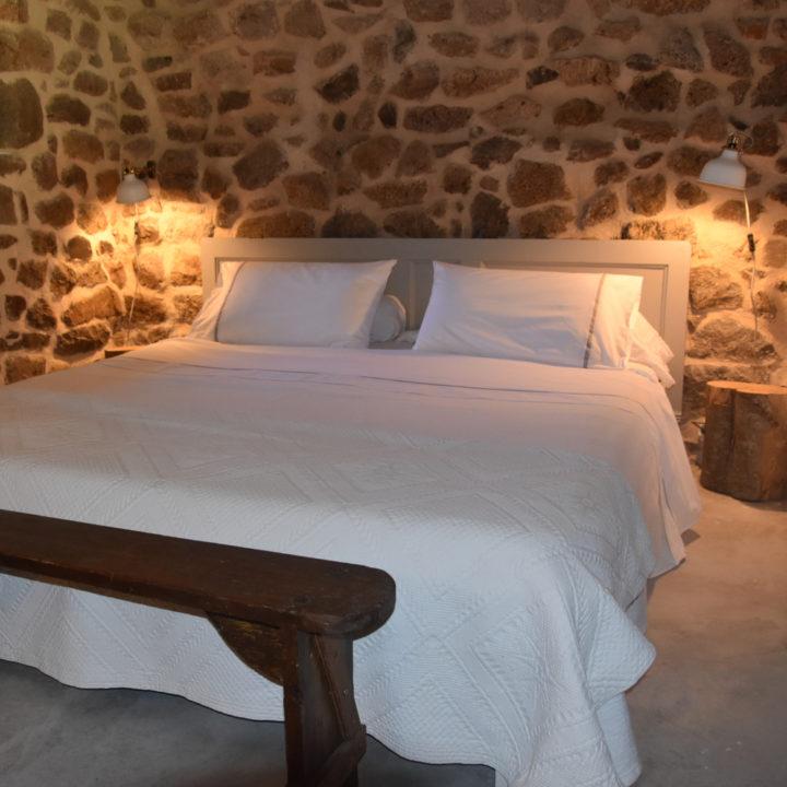 Tweepersoons bed met wit beddengoed, een houten bankje aan het voeteneinde en stoere gewelven.